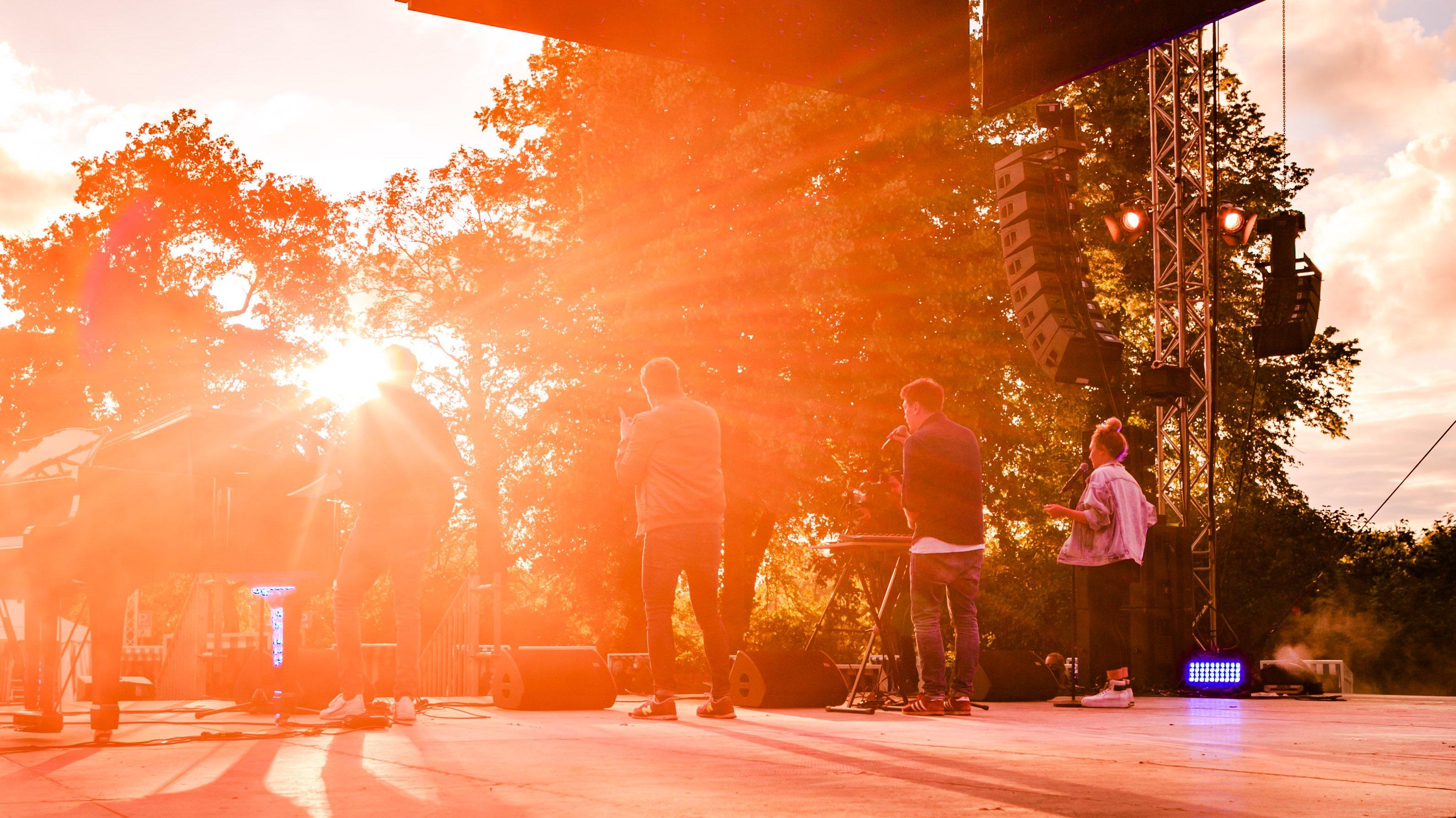 Zu sehen ist die Bühne des Kick-Off Events in Eutin. Die Band Stanfour spielt im Sonnenuntergang für das Publikum.