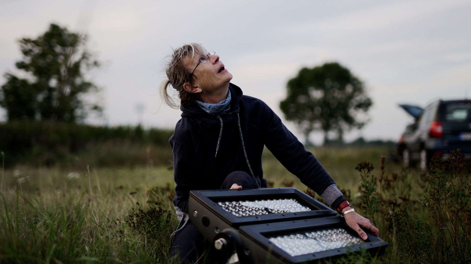 Die Lichtkünstlerin Gisela Meyer-Hahn setzt eine Windkraftanlage mit Lichteinstellungen in Szene. Das Filmteam von Moritz Boll nimmt Frau Meyer-Hahn gerade an Ihrem Mischpult vor der Windkraftanlage auf.