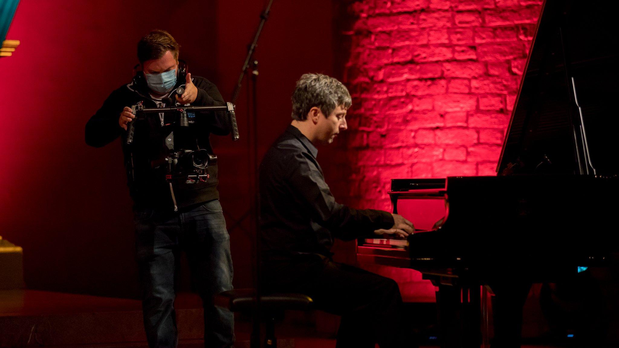 Pianist Daniel Fritzen wird bei seinem Konzert in der Kirche Flensburg von einem Kameramann gefilmt.