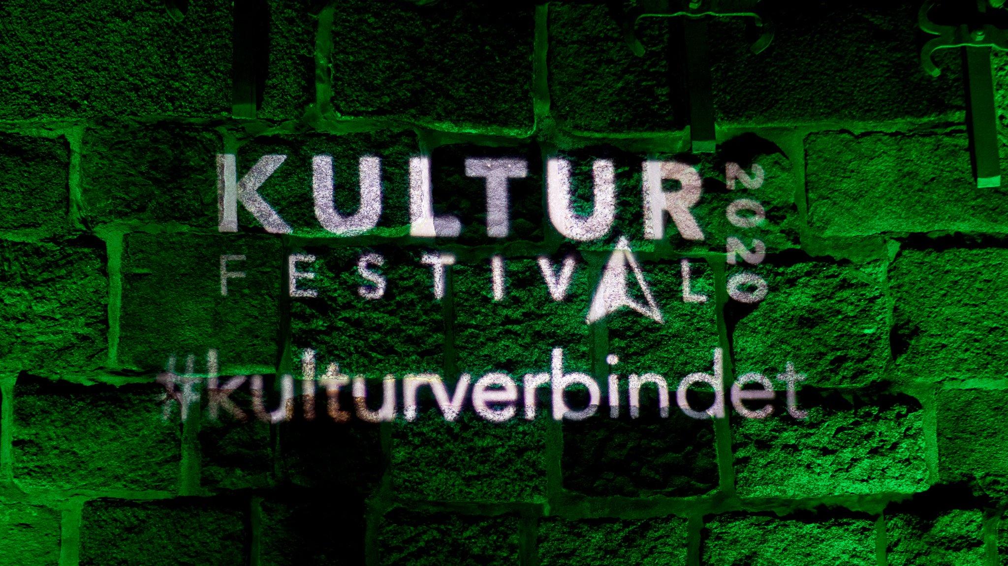 Das Kulturfestival-Logo auf einer grün illuminierten Mauer.